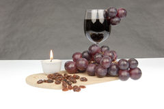 Red wine grapes and raisins with candle Royalty Free Stock Image