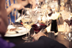 Red wine on hand with dinner on restaurant Royalty Free Stock Photo