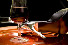 Red wine and high heel shoes on a tray Royalty Free Stock Image