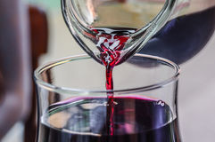 REd wine in the jar. Glass and jug of red wine in process of pouring Royalty Free Stock Images