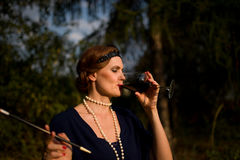 The Red Wine Lady in the garden - 1930 Style. The Lady - 1930 Style is drinking the red wine in the garden Stock Images