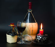 Red wine. Large and small bottles of red wine decorated with knitted leaves light bamboo castanets and the Spanish small dome on the lid of a small bottle in the Stock Photo