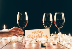 Red wine and merry christmas card. Female hand holding a wine glass over wooden table with fairylights, candles and merry christmas card Royalty Free Stock Images