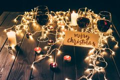 Red wine and merry christmas card. Three glasses with red wine on wooden table with fairylights, candles and merry christmas card Stock Image