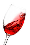 Red wine in motion. Red wine swirling around a wine glass isolated on white Stock Image