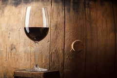 Red wine near a barrel. Glass of red wine standing near an old wooden barrel in a cellar stock photos