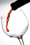 Red wine penetration. Wine jet entering wine glass on white background Royalty Free Stock Photo