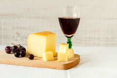 Red wine and a piece of cheese. Still life composition with red wine and homemade rustic cheese Stock Photography