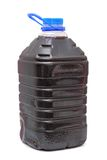 Red wine in plastic container. Homemade red wine in plastic container with blue cap over white background Royalty Free Stock Photos