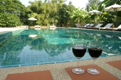 Red wine pool side. Red wine glasses on swimming pool side Royalty Free Stock Photos