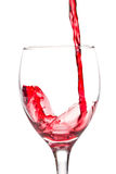 Red wine poriung into a wine glass. Pouring red wine into a wine glass on a white background Royalty Free Stock Photos