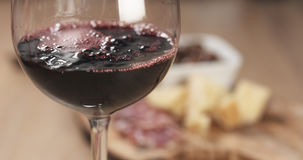 Red wine pour in front of italian antipasti appetizers. Wide photo Royalty Free Stock Images