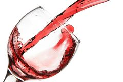 Red wine pour into glass. Close-up isolated over white background Stock Photo
