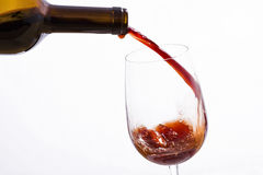 Red wine poured from a bottle into a wine glass Royalty Free Stock Image