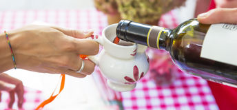 Red wine poured into ceramic jug. In Chiavenna, during the festivanl named La sagra dei crotti, red wine poured into ceramic jug Stock Photos
