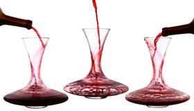 Red wine poured into decanter. On white background Stock Photos