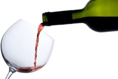 Red wine poured into a glass. Red wine pouring down from a wine bottle stock images
