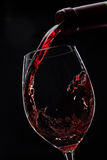 Red wine poured into glass. On black Royalty Free Stock Photo