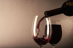 Red wine poured. Into a glass on background Stock Images