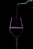 Red wine. Poured into a glass on a black background Royalty Free Stock Photo