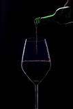 Red wine. Poured into a glass on a black background Royalty Free Stock Photography