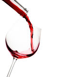 Red wine poured in a glass. Isolated on white Royalty Free Stock Photography