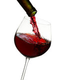 Red wine poured in a glass. Isolated on white Stock Photography