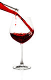 Red wine poured in a glass. Isolated on white Royalty Free Stock Photo