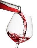 Red wine poured in a glass. Isolated on white background Royalty Free Stock Images