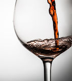 Red wine poured into glass standing on gray background Stock Photos