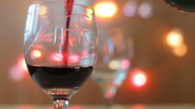Red wine poured into glass. Two glasses, lights background stock video