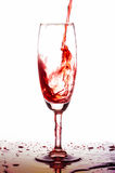 Red wine poured in a glass on white backgroubd. Royalty Free Stock Photography