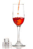 Red wine is poured into a glass On a white background Stock Images