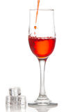 Red wine is poured into a glass On a white background Stock Image