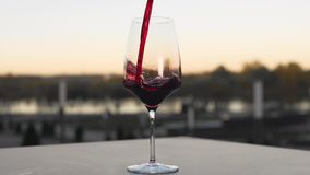 Red wine is poured to the wineglass outdoors in slow motion, bar and restaurant, alcohol drinks, food in slow motion