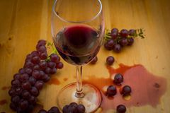 Red wine poured into wine glass and spilled on wooden table with fresh grapes as background design stock image