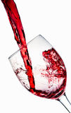 Red wine poured into wine glass. White background Stock Photography