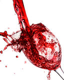 Red wine poured into wine glass. On a white background Stock Photo
