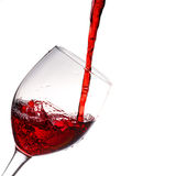 Red wine poured into wine glass. On a white background Royalty Free Stock Photo