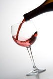 Red wine pouring. Into wineglass isolated on white background Stock Photos