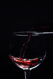 Red wine pouring. Into a wineglass. Isolated on black background Stock Photo
