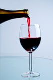 Red wine pouring from bottle. Into wine glass Stock Photos