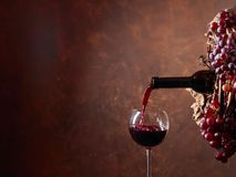 Red wine pouring from a bottle into a glass. Wreath of vine with juicy grapes. Conceptual image on the theme of winemaking. Copy space for your text stock image