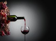 Red wine pouring from a bottle into a glass. Wreath of vine with juicy grapes. Conceptual image on the theme of winemaking. Copy space for your text stock photo