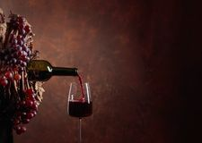 Red wine pouring from a bottle into a glass. Wreath of vine with juicy grapes. Conceptual image on the theme of winemaking. Copy space for your text stock photography