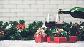 Red wine is pouring from bottle in to glass decorating with red gift boxes and Christamas ornaments. Copy space at top area with. Blurred white brick wall royalty free stock image