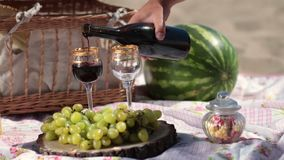 Red wine pouring in crystal glasses on picnic stock video