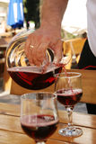 Red wine pouring from decanter. Waiter pours red wine from decanter into wineglasses outdoors Stock Photos