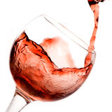 Red wine pouring down. From a bottle isolated on white royalty free stock image