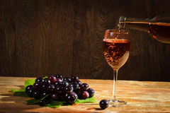Red wine pouring down to the glass with grapes Stock Photos